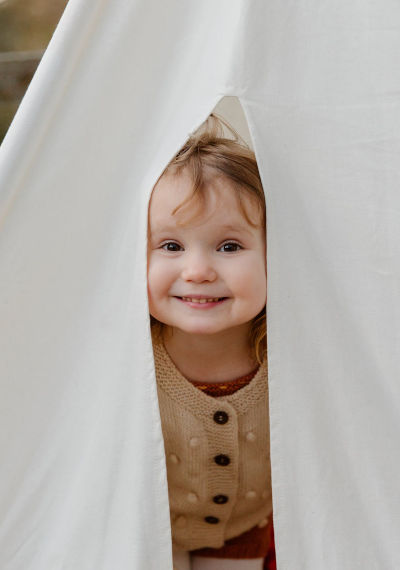 A little girl looking out of a tent